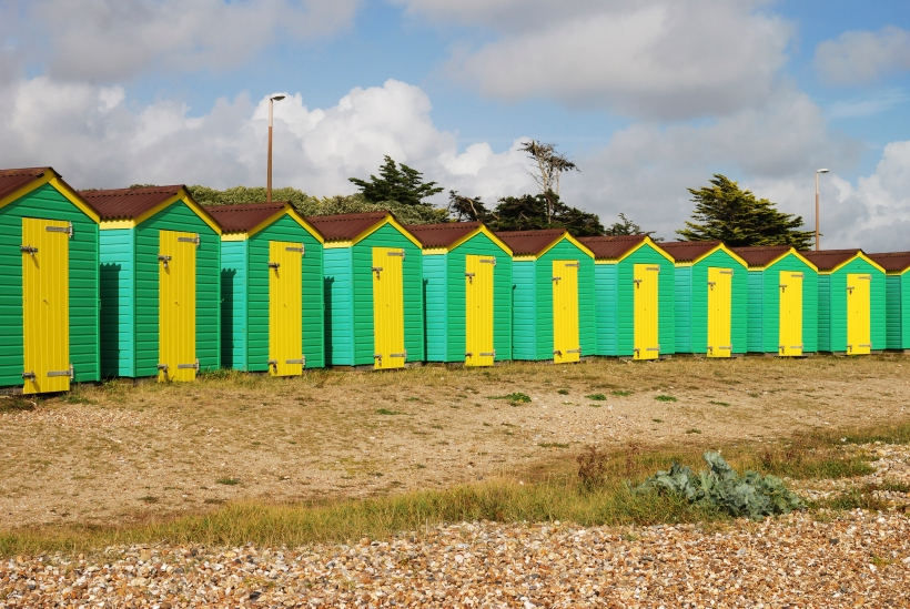 Green and yellow painted beach huts on the seafront at Littlehampton. West Sussex. England